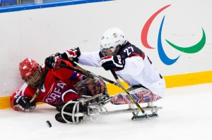Photo by Ken King  USA Sled Hockey player, Josh Pauls, checks Korea into the boards to gain the puck.  USA wins 3-0