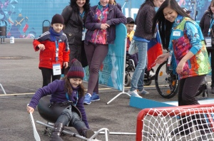 photo by Katie Harris A Sochi 2014 volunteer helps kids learn more about Sled Hockey.